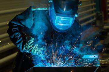 Foto op Plexiglas Body Paint Welder welds metal parts in a protective suit