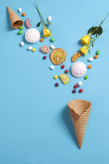 Marshmallows, candy, jelly beans, sweets and dry mugs oranges falling in wafer cone on blue background