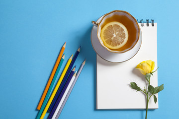 Square notepad on springs with white kraft paper, pencil, yellow rose and cup of tea are on a blue background.