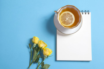 Square notepad on springs with white kraft paper, yellow rose and cup of tea are on a blue background.