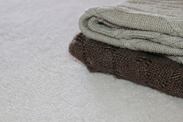 Stack of cozy knitted warm sweater on your home background . Sweaters in retro Style. The concept of warm .