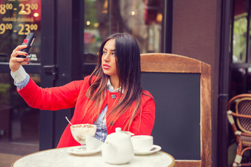 Woman with phone taking a picture of herself. Girl i a cafe, restaurant, coffee shop.