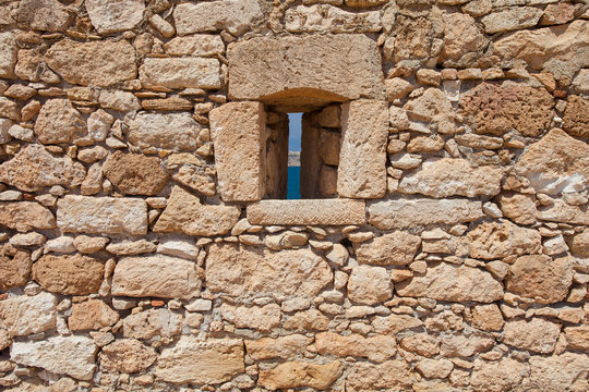View on the stone wall with a narrow window of Fortezza Castle in Rethymnon
