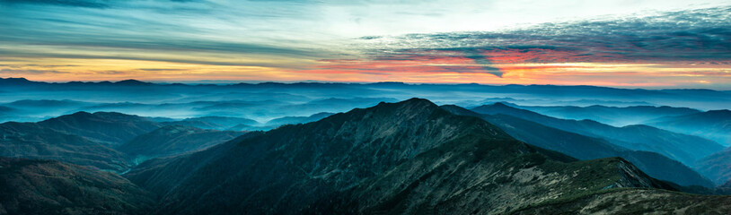 Panorama with blue mountains and hills at sunset