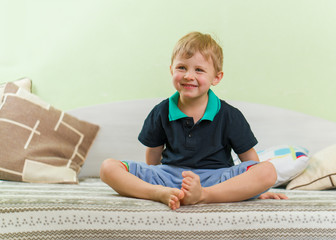 Skinny blond boy smiling heartily, sitting on a bed in the children's room, crossed legs. Dressed in a casual black shirt and blue pants.