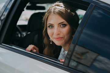 close-up portrait of a pretty shy bride in a car window