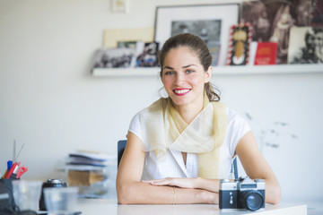 Beautiful woman photography professional is smiling, seating on her desk, with a vintage camera, while in a modern working environment