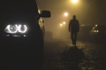 The car headlight with a walking man on the background of a fog Fotomurales