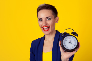 Anticipation. Headshot young funny looking excited business woman holding alarm clock waiting isolated yellowwall background. Human face expressions emotions. Time punctuality busy schedule concept