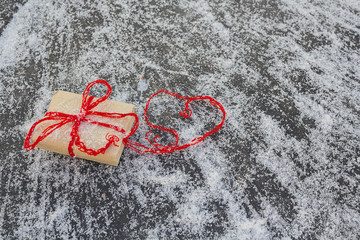 Gift and red hearts on a wood surface
