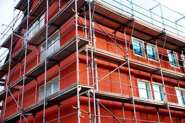 Haus mit Gerüst, roter Fassadenanstrich