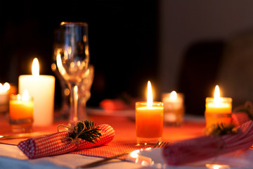 Festive composition with candles and plates. Table decoration. A beautiful table setting, red table cloth, tablecloth in a cage. Christmas dinner. A white plate with a nice napkin on the table