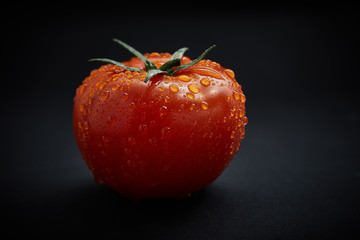Fresh tomato on black background