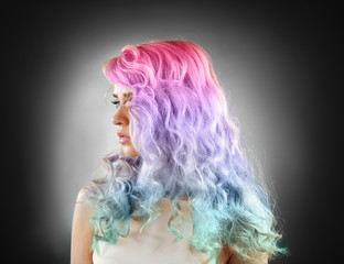 Trendy hairstyle concept. Young woman with colorful dyed hair on gray background