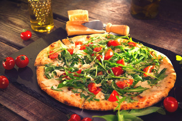 Pizza Caprese with arugula, cheese, yoghurt and cherry tomatoes. Homemade delicious vegetarian pizza on wooden table