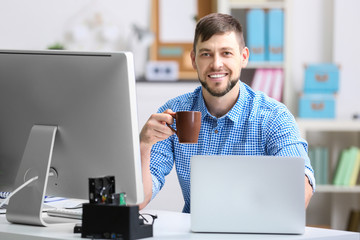 Handsome young programmer working in office - fototapety na wymiar