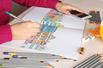 Woman sitting at table with coloring book for adults, closeup