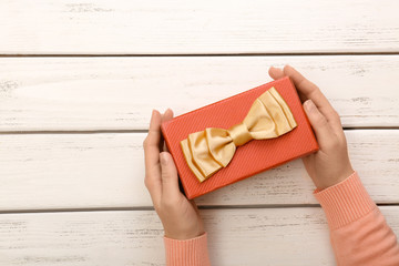Female hands holding gift box, on wooden background
