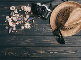travel background. Men's style hat, compass, seaShell and camera on a wooden background