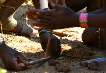 Hadzabe men lighting a fire by hand drill