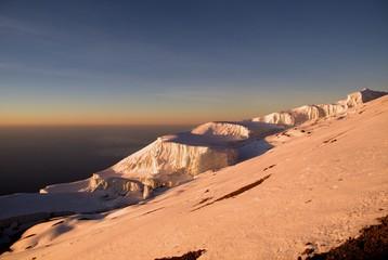 Orange glow across the upper slopes of Mt Kilimanjaro at sunrise.
