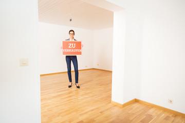 Realtor In Empty Apartment, Holding 'zu Verkaufen' Sign