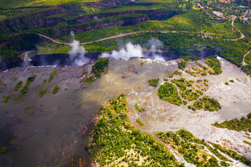 Wall Mural - Aerial view of the Zambezi river right before Victoria Falls.  Clouds and mist rising up from the falls.