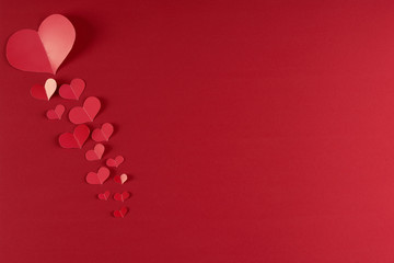 Red hearts on a red background. Love card concept with copy space, Valentine's day theme. Shot from above