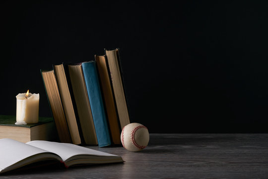 Blank notebook, books, baseball ball and candle on wooden table against black. Education, knowledge concept with copy space