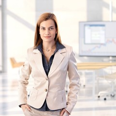 Confident young businesswoman at bright office
