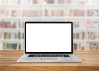 Laptop with blank screen on table. interior background, bookshel