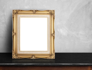 Blank Gold victorian picture frame on black marble table at grey
