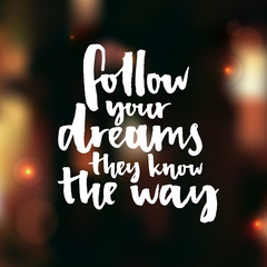 Follow your dreams, they know the way. Inspirational quote about life and love. Modern calligraphy text on night blur background.