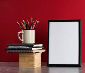 Desk with blank white picture frame and pencils in iron mug placed on books and wooden box. Red background