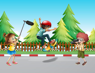 Children shooting vdo with boy skateboarding