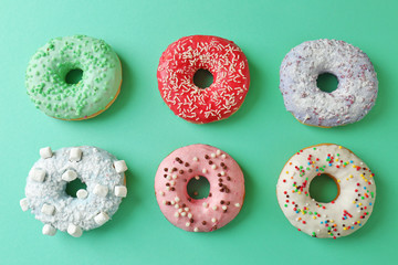 Delicious donuts on color background