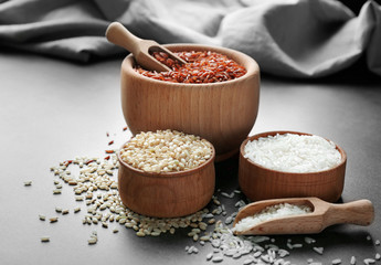 Different types of rice in wooden bowls on grey table