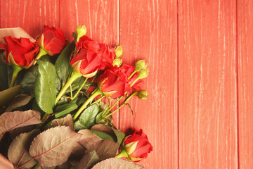 Beautiful red roses on wooden background