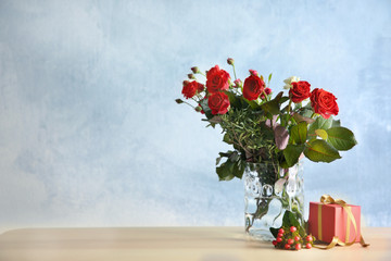 Beautiful red roses in a vase on color background