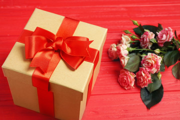 Gift box with flowers on wooden table