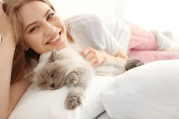 Beautiful young woman with cute cat lying on bed at home