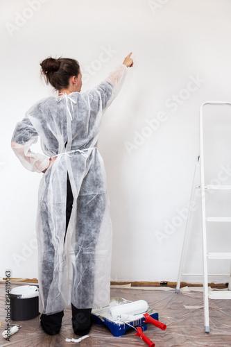 frau beim streichen zeigt auf die frisch gemalte wand stockfotos und lizenzfreie bilder auf. Black Bedroom Furniture Sets. Home Design Ideas