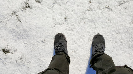Closeup of sneakers men's stomp on the ground covered with snow in the winter.