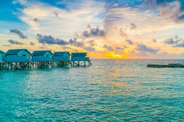 Beautiful water villas in tropical Maldives island at the sunset