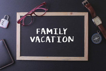 FAMILY VACATION WORD ON BLACKBOARD WITH WATCH,PASPORT, GLASS