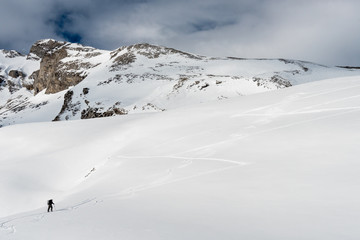 FORMIGAL, SPAIN - JUNE 20, 2017:  a mountain skier walks ahead using his skis and skins through a snowy valley in the vicinity of Formigal, Tena Valley, Spanish Pyrenees.