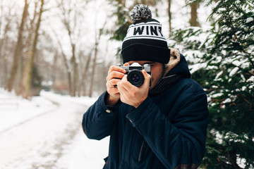 A young man in black and white hat and blue jacket makes the photo on the retro camera in winter Park