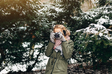 A young woman in a green jacket, gray gloves and scarf making photo retro camera in winter park on a background of of Christmas tree