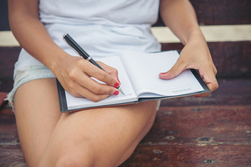 Young beautiful woman writing on notepad while sitting on the be