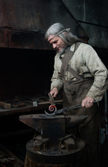 Old gray blacksmith forges the metal product in the smithy